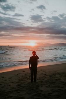 해변에서 석양을 바라보는 남자