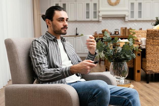 Человек смотрит телевизор и ест попкорн, вид сбоку