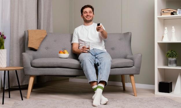 Человек смотрит телевизор и ест попкорн