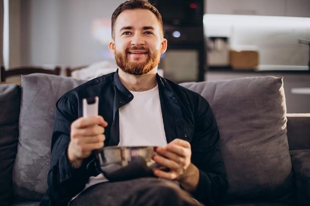 Человек смотрит телевизор дома и сидит на диване