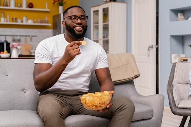 Uomo che guarda la tv e mangia patatine