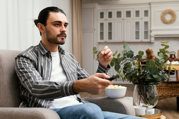 Man watching tv and eating popcorn side view