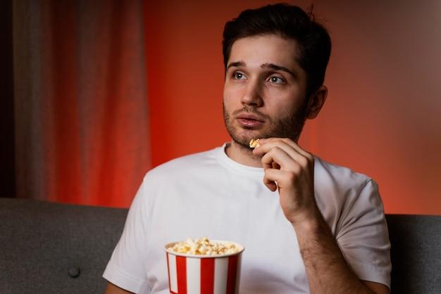 Uomo che guarda la tv e mangia popcorn