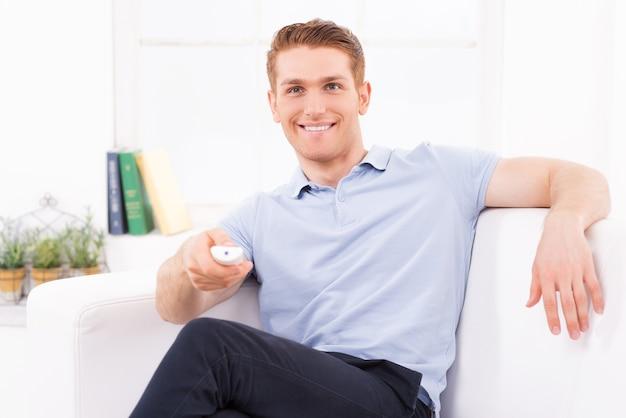 テレビを見ている男。ソファに座って、リモコンを手に持ってテレビを見ているハンサムな若い男