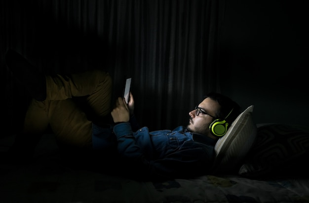 Man watching tv series in a tablet sitting on a bed in the night at home