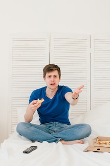 Man watching tv sitting on the bed and eating pizza
