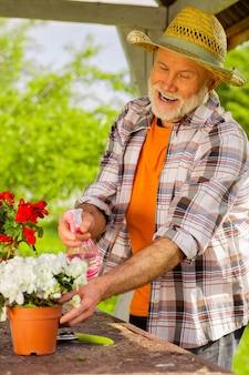꽃을 급수하는 남자. 밖에 서있는 냄비에 꽃에 물을 주면서 즐거운 느낌을주는 수염 난 은퇴 한 남자