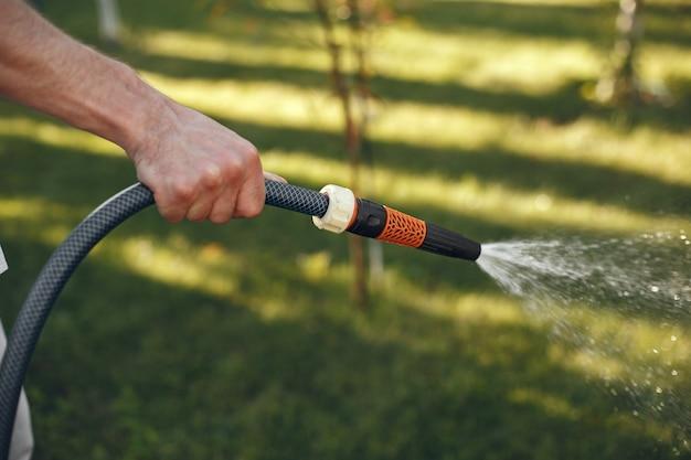 Мужчина поливает растения в своем саду. мужчина в голубой рубашке.
