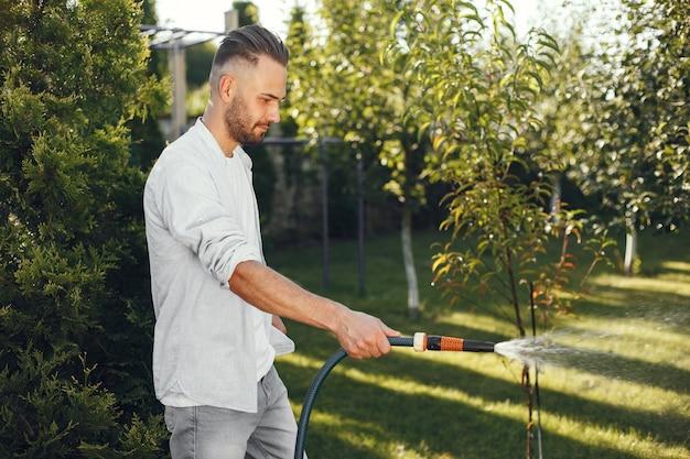 彼の庭で彼の植物に水をまく男。青いシャツを着た男。