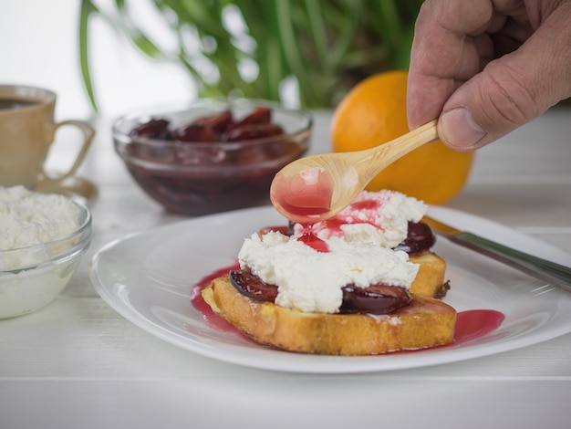 Man watering plum jam toasted french bread with curd cream.