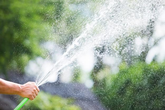 화창한 날에 호스에서 정원에 물을주는 남자