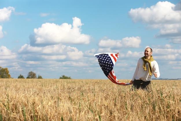 Человек размахивает американским флагом, стоящим в сельскохозяйственном поле фермы травы, праздники, патриотизм, гордость, свобода, политические партии, иммигрант