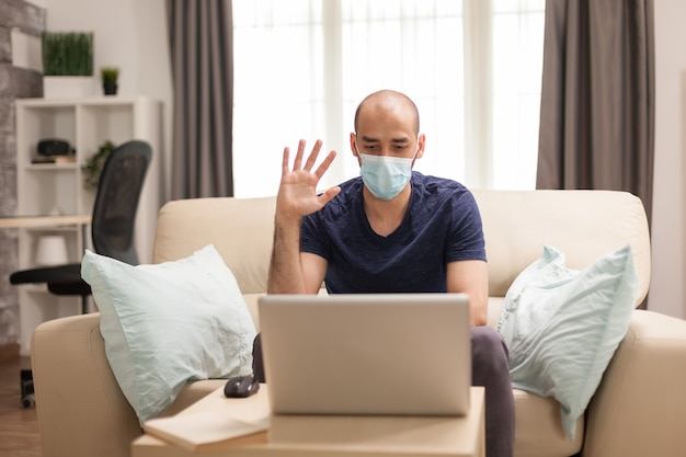 Man waving during a video conference while wearing a protection mask in time of global pandemic.