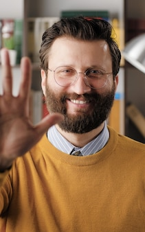 Man waving hello. positive smiling laughing man in office or apartment room looking at camera and waving right hand showing and says greeting hi. close-up view