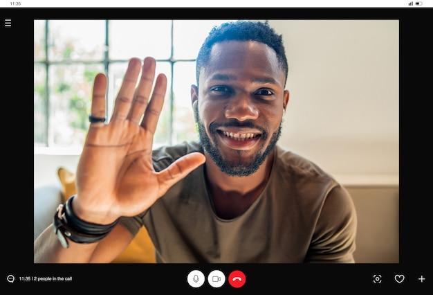 自宅でビデオ通話をしながら手を振って誰かに挨拶する男。新しい通常のライフスタイルのコンセプト。