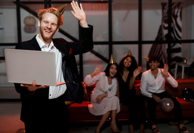 Мужчина машет рукой во время видеочата с друзьями на новогодней вечеринке