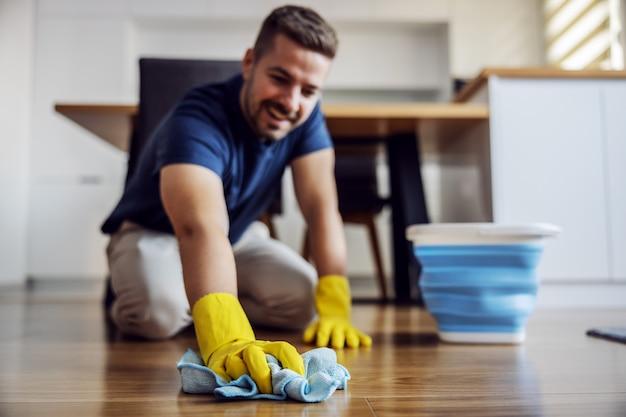 自宅で寄木細工の床をワックスの男。手にゴム手袋。ホームインテリア。