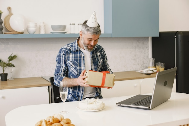 男はパーティーハットをかぶる。男はギフトの入った箱を持っています。男はラップトップを介して電話をかけます。