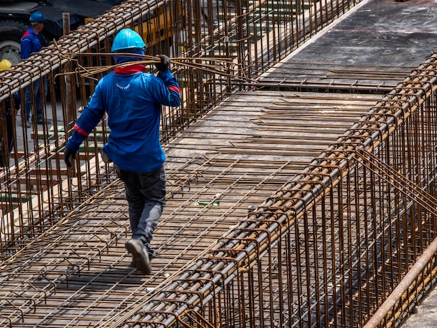 The man wear blue long-sleeve shirts, wear helmets work in construction area