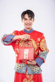 男は伝統的な日に驚くべきために妹に赤いバッグを与える準備ができているチャイナドレスを着ています