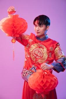 チャイナドレスの男性が中国の旧正月で買い物をするために赤いランプを飾る