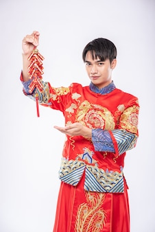 L'uomo indossa il sorriso cheongsam per ottenere petardi dal capo nel capodanno cinese