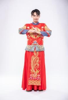 L'uomo indossa un sorriso cheongsam ed è in piedi e rispetta i clienti che vengono a fare acquisti nel capodanno cinese