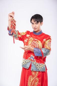 남자는 중국 새해에 상사로부터 폭죽을 얻기 위해 치파오 미소를 입는다.