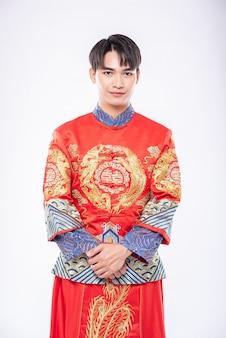 남자는 중국 새해에 여행자 쇼핑을 환영하기 위해 cheongsam 미소를 입는다.