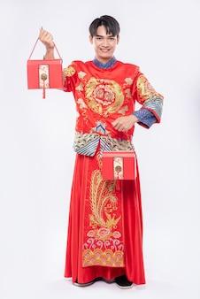 Мужчина в костюме cheongsam и черной обуви рад получить красную сумку для сюрпризов в китайском новом году
