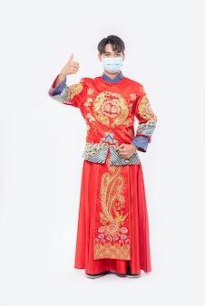 Мужчина в костюме и маске cheongsam показывает лучший способ делать покупки для защиты от болезней
