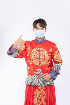 치파오 수트와 마스크를 착용 한 남성, 질병 보호를 위해 쇼핑하는 가장 좋은 방법