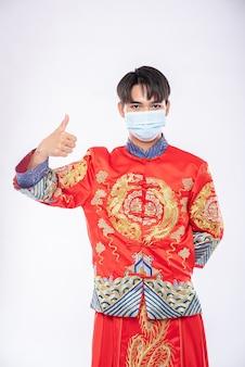 男はチャイナドレスのスーツとマスクを身に着けて病気を守るために買い物をする最良の方法を示しています
