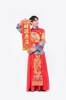 男はチャイナドレスのスーツを着て、黒い靴を履いて、家族に中国の旧正月の幸運のために中国のグリーティングカードを与えます
