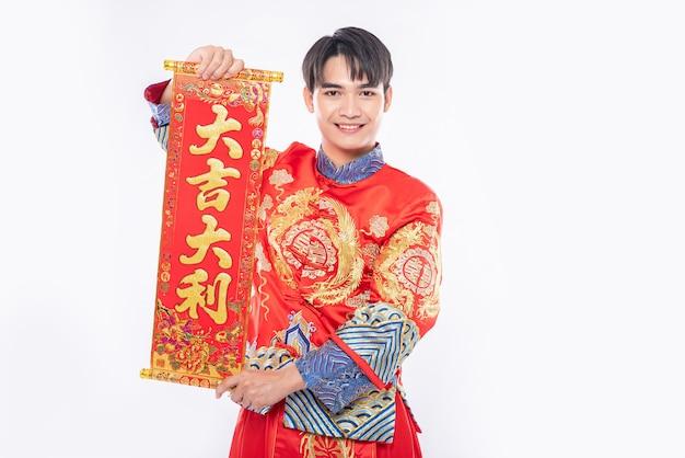 L'uomo indossa il vestito cheongsam dà alla famiglia il biglietto di auguri cinese per fortuna nel capodanno cinese