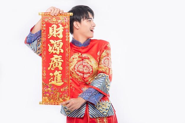 男はチャイナドレスのスーツを着て、家族に中国の旧正月の幸運のために中国のグリーティングカードを与える