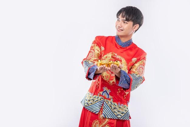 チャイナドレスを着た男が中国の旧正月の幸運のために彼の親戚に金を与える
