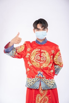Man wear cheongsam suit and mask show the best way to shopping for protecting disease