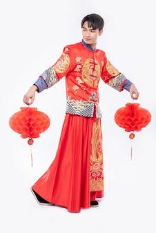 Мужчина в костюмах cheongsam украсил свой магазин красной лампой в китайском новом году