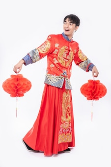 チャイナドレスの男性が中国の旧正月に彼の店に赤いランプを飾るスーツショーを着用