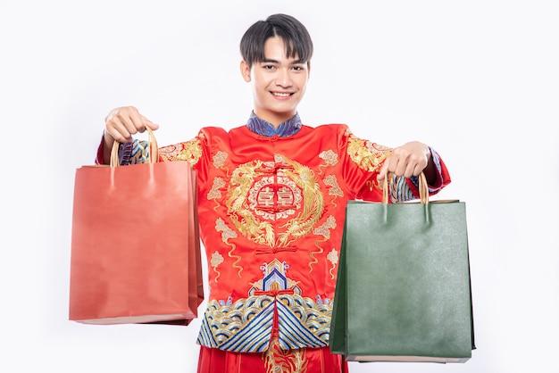 L'uomo indossa il sorriso del vestito cheongsam con il sacchetto di carta dallo shopping nel capodanno cinese