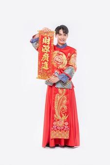 L'uomo indossa un abito cheongsam e indossa una scarpa nera dà alla famiglia il biglietto di auguri cinese per fortuna nel capodanno cinese