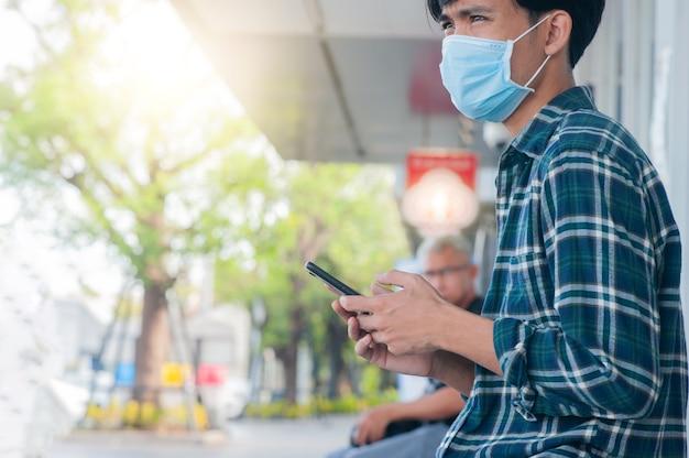 남자는 모바일 스마트폰을 사용하여 안면 마스크를 착용