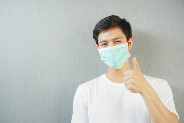 Man wear face mask with showing thumb up