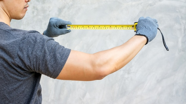Man wear a glove and holding a measuring tape.