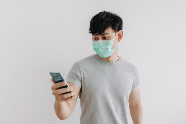 男はマスクを着用し、白い背景で隔離の電話アプリケーションを使用しています