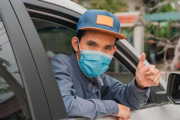 男は車の中で医療用マスクを着用