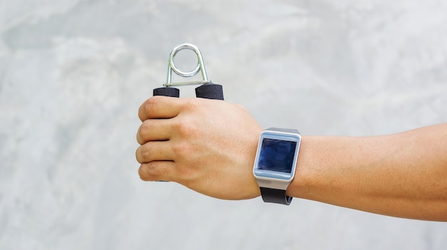 Man wear a smartwatch and use handgrips for exercise.