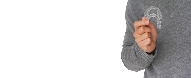 Мужчина носит свитер и поднимает руку, держащую фиксатор зубного элайнера
