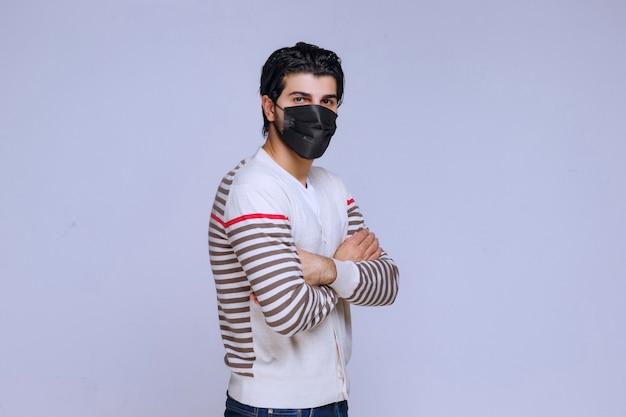 그의 팔을 교차하는 검은 마스크를 착용하는 남자.